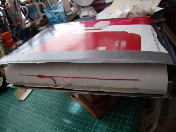 The three signatures sewn to the spine inner with the cardboard cover balanced precariously on top - so you get the idea!